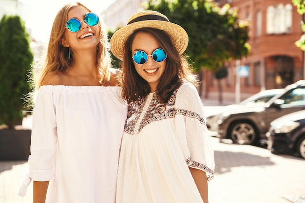 Fashion portrait of two young stylish hippie brunette and blond women models in summer sunny day in white hipster clothes posing . going crazy