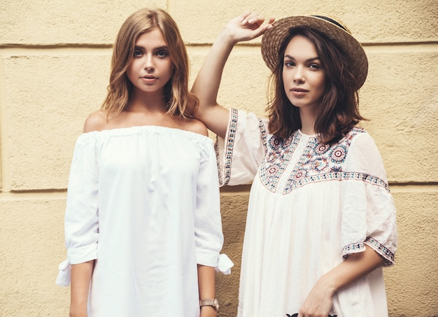 Fashion portrait of two young stylish hippie brunette and blond women models in summer sunny day in white hipster clothes posing near yellow wall. no makeup