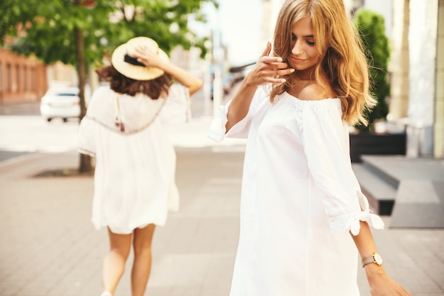 Fashion portrait of two young stylish hippie brunette and blond women models in summer sunny day in white hipster clothes posing . no makeup