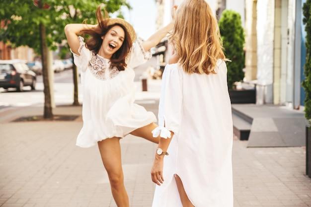 Adatti un ritratto di due modelli di donne castane e bionde di giovane hippy alla moda nella posa bianca del vestito dai pantaloni a vita bassa dell'estate. i migliori amici si sono incontrati