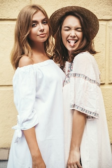 Fashion portrait of two young stylish hippie brunette and blond women models in summer white hipster dress posing near yellow wall. no makeup. showing tongue