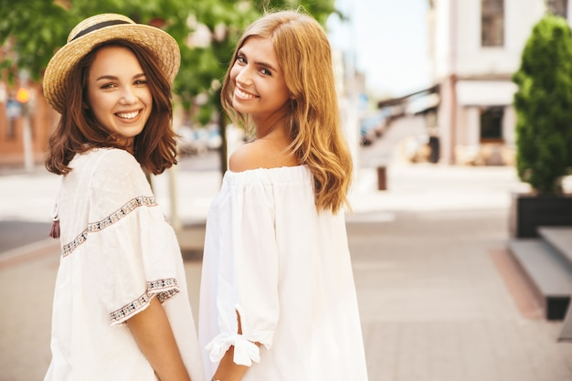 Fashion portrait of two young stylish hippie brunette and blond women models without makeup in summer sunny day in white hipster clothes posing . turn around