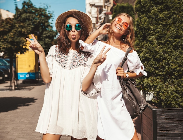 Fashion portrait of two young stylish hippie brunette and blond women in summer sunny day. models dressed in white hipster clothes. womans posing