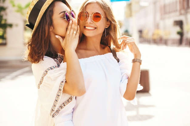 Fashion portrait of two young stylish hippie brunette and blond women in summer sunny day in white hipster clothes posing