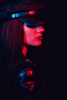 Fashion portrait of a woman in profile in a leather cap and jacket with a red neon light