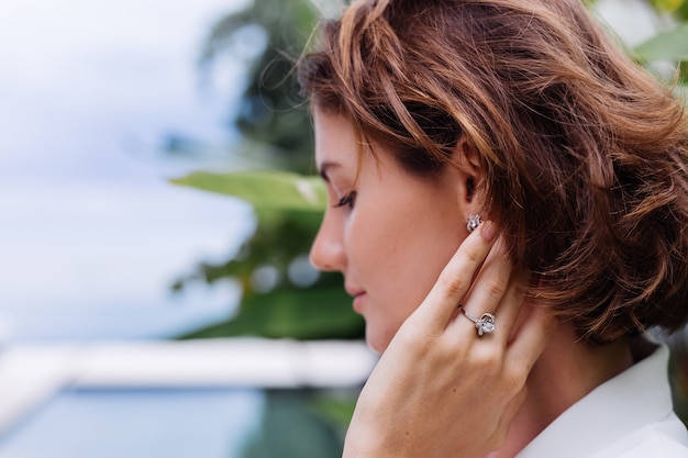 Fashion portrait of woman at tropical luxury villa wearing white stylish blazer and jewellery over tropical leaves