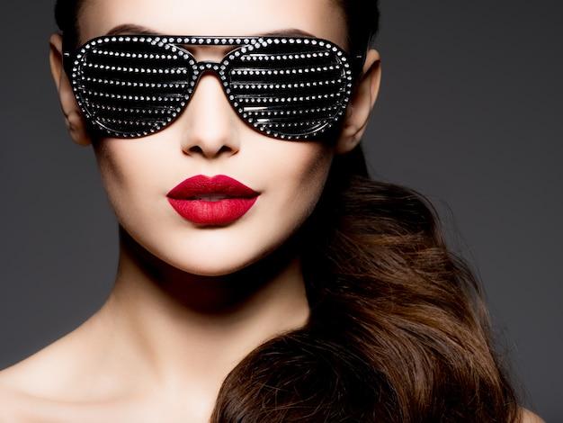 Moda ritratto di donna che indossa occhiali da sole neri con diamanti e labbra rosse
