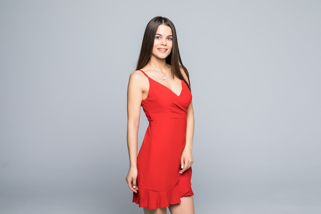 Fashion portrait of woman with long hair in red dress isolated on gray wall. Free Photo
