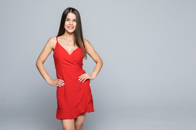 Fashion portrait of woman with long hair in red dress isolated on gray wall.