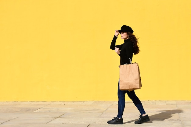 Fashion portrait woman with shopping bags wearing black outfit with hat posing on yellow wall.