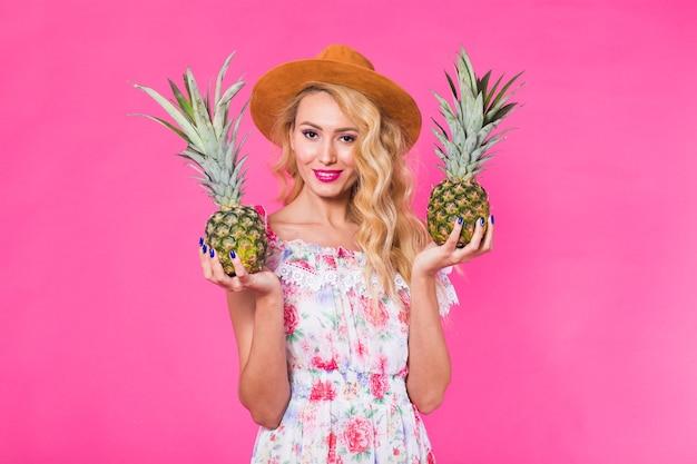 Мода портрет женщины с солнцезащитными очками и ананасом на розовом