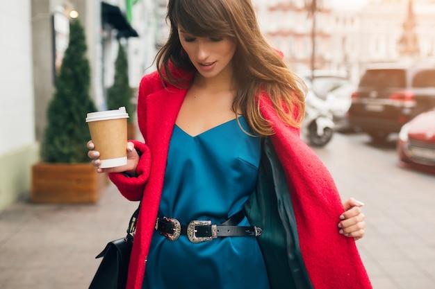 Moda ritratto di giovane bella donna elegante che cammina nella strada della città in cappotto rosso, tendenza stile autunnale, bere caffè, sorridente, felice, vestito di seta blu