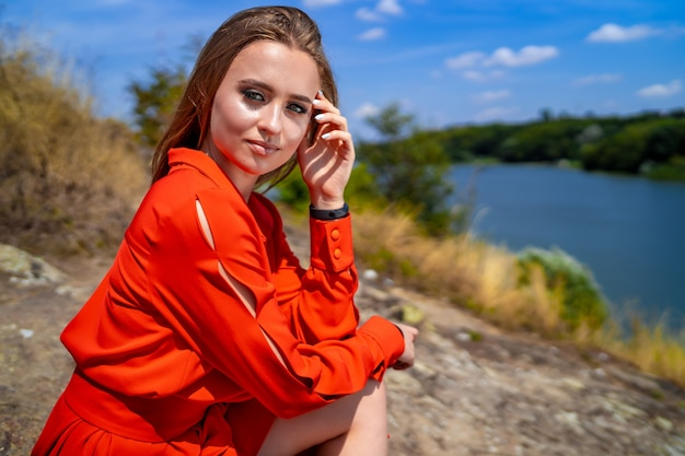 Fashion portrait of young beautiful woman in red dress posing in nature.