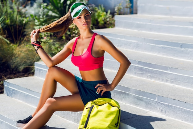 Fashion portrait of young beautiful woman in stylish sports uniform with neon backpack and transparent visor posing near gym in sunny summer day.