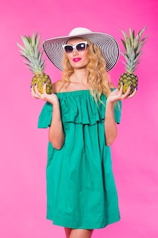 Fashion portrait young beautiful woman with pineapple over pink background