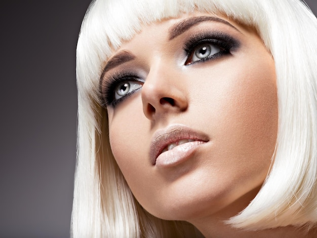 Moda ritratto di giovane bella donna con i capelli bianchi e il trucco dell'occhio nero