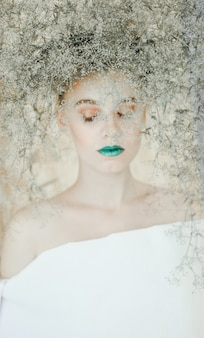 Fashion portrait of young blond woman .beautiful woman with green lips. concept of mother nature