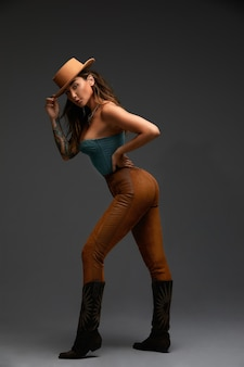 Fashion portrait of young brunette woman in blue western top and jeans with cowboy hat and boots