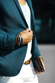 Fashion portrait of young businessman handsome  model man in casual cloth suit with accesories on hands