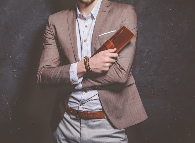 Fashion portrait of young businessman handsome model man dressed in elegant brown suit with accessories