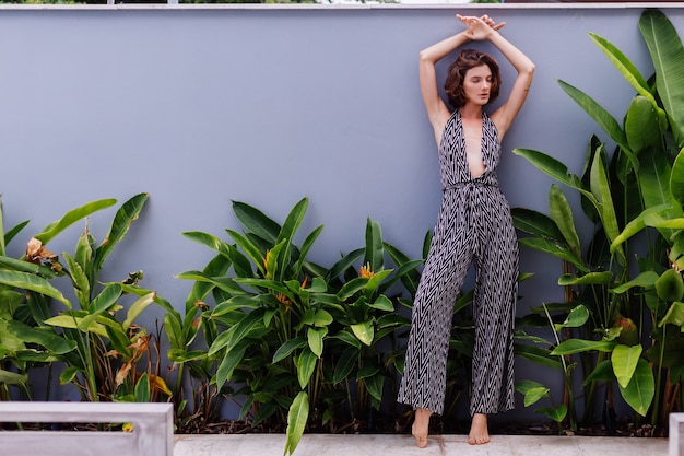 Fashion portrait of young caucasian stylish model woman in classic long jumpsuit posing on wall and tropical leaves natural light outdoor