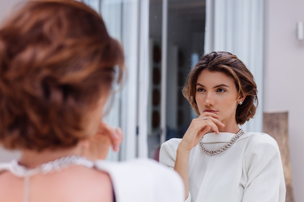 Fashion portrait of young caucasian woman professional model in white blazer and silver chain look in mirror at luxury villa