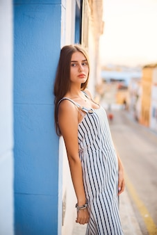 Fashion portrait of young elegant woman posing against the blue wall.