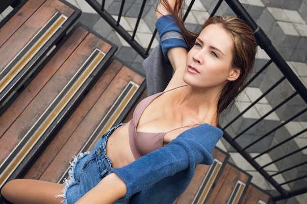 Fashion portrait of a young fashionable woman, dressed in sports and top, posing on the stairs, enjoys rest in a city, summer street fashion. portrait of a joyful woman