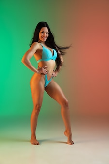 Fashion portrait of young fit and sportive caucasian woman in stylish blue swimwear on gradient background. brunette longhair model. perfect body ready for summertime. beauty, resort, sport concept.