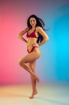 Fashion portrait of young fit and sportive caucasian woman in stylish red swimwear on gradient