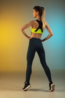 Fashion portrait of young fit and sportive woman on gradient background. perfect body ready for summertime.