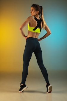 Fashion portrait of young fit and sportive woman on gradient background perfect body ready for