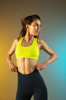 Fashion portrait of young fit and sportive woman on gradient background