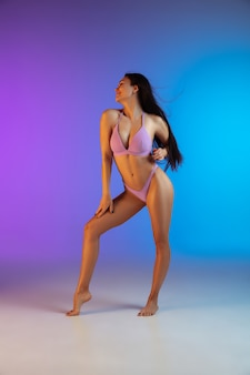 Fashion portrait of young fit and sportive woman in stylish luxury swimwear on gradient. perfect body ready for summertime.