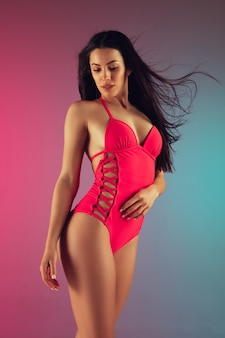 Fashion portrait of young fit and sportive woman in stylish pink luxury swimwear on gradient. perfect body ready for summertime.