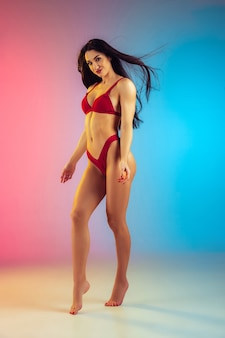 Fashion portrait of young fit and sportive woman in stylish red luxury swimwear on gradient wall perfect body ready for summertime