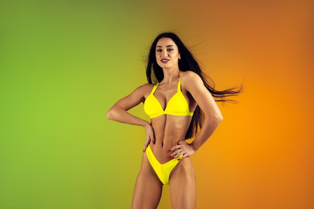 Fashion portrait of young fit and sportive woman in stylish yellow luxury swimwear on gradient wall perfect body ready for summertime