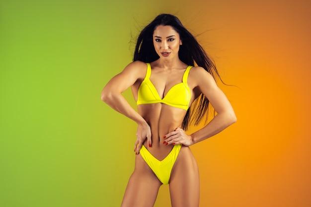 Adatti il ritratto di giovane misura e la donna allegra in costume da bagno di lusso giallo alla moda. corpo perfetto pronto per l'estate.
