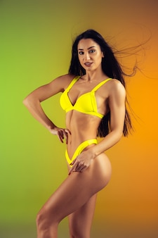 Fashion portrait of young fit and sportive woman in stylish yellow luxury swimwear. perfect body ready for summertime.