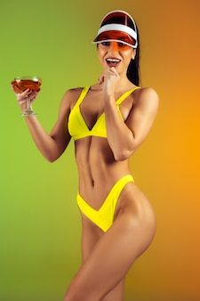 Fashion portrait of young fit and sportive woman with cocktail in stylish yellow luxury swimwear on gradient wall perfect body ready for summertime
