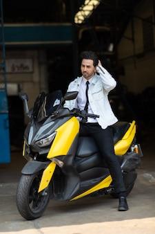 Мода портрет молодой красивый парень позирует на мотоцикле