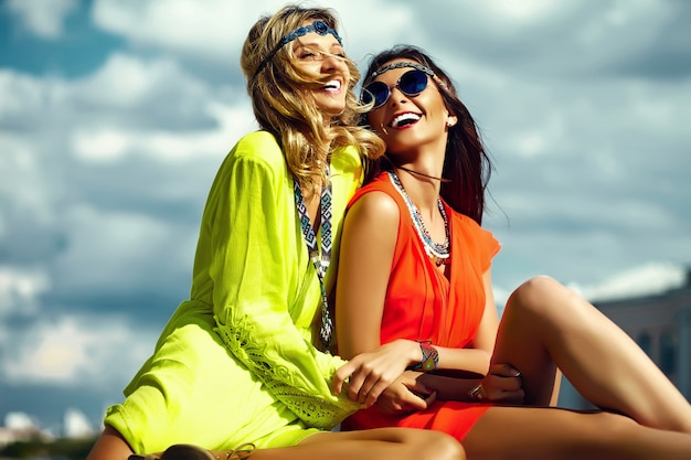 Fashion portrait of young hippie women girls in summer sunny day in bright colorful cloth