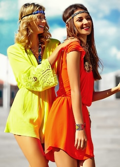 Fashion portrait of young hippie women models in summer sunny day in bright colorful hipster clothes