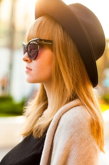 Fashion portrait of young hipster woman with hat and sunglasses on the beach at sunset, retro style color tones cold season. warm clothes.