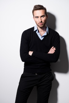 Moda ritratto di giovane uomo in pullover nero e camicia blu con le braccia incrociate