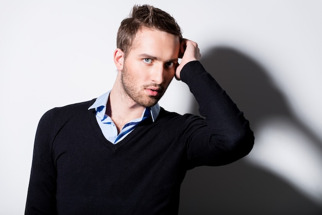 Fashion portrait of young man in black pullover poses over wall with contrast shadows.