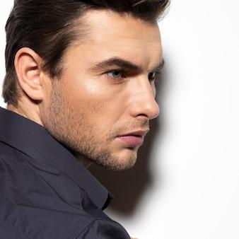 Moda ritratto di giovane uomo in camicia nera pone sul muro con ombre di contrasto