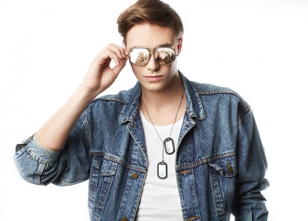 Fashion portrait of the young man wearing jeans jaket