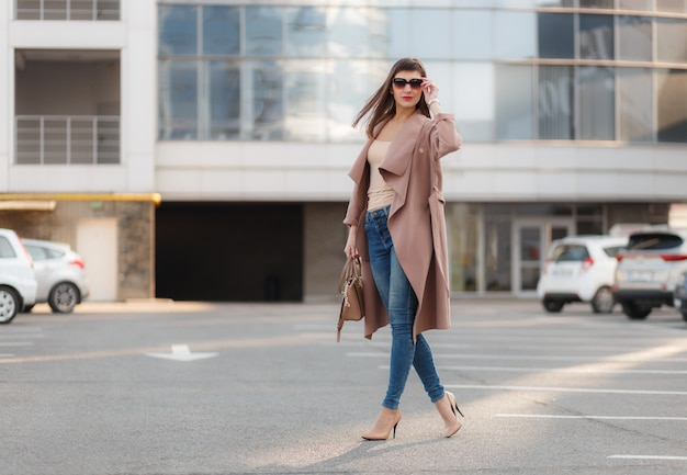Fashion portrait of young model woman in nice brown beige coat, denim jeans and sunglasses