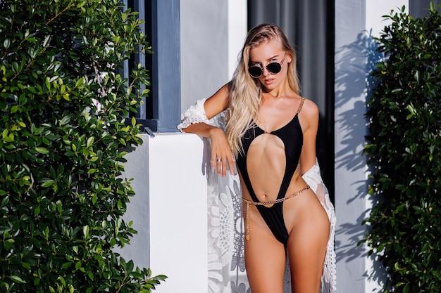 Moda ritratto di giovane donna europea ricca ed elegante in costume da bagno alla moda nero, occhiali da sole e mantello di pizzo fuori dalla villa, sfondo tropicale, luce calda del tramonto